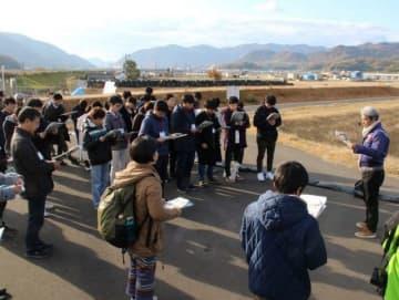 拡幅された小田川の堤防で、被災・復旧状況についての説明を聞く大学生=倉敷市真備町箭田