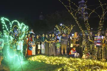 福岡市とヤンゴン市の姉妹提携3年を記念して披露されたライトアップに見入る人々=7日、ヤンゴン(共同)