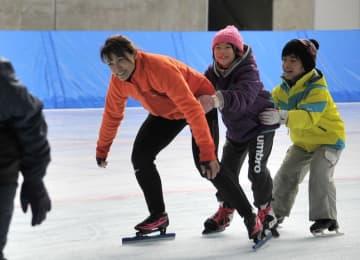 岡崎朋美さん(左)を手本に、低い姿勢を意識した滑りを練習する子どもたち=7日、YSアリーナ八戸