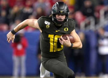 SANTA CLARA, CALIFORNIA - DECEMBER 06: Quarterback Justin Herbert #10 of the Oregon Ducks runs with the ball against the Utah Utes during the first half of the Pac-12 Football Championship Game at Levi's Stadium on December 06, 2019 in Santa...