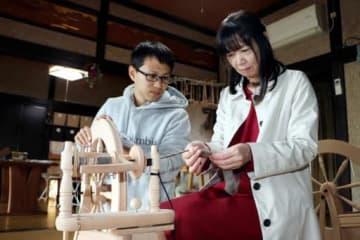 体験会で、参加者に毛糸紡ぎの指導をする山田さん(左)