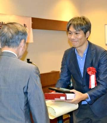 賞状と記念の盾を受け取る阿部岳編集委員=7日、東京・内幸町の日本プレスセンタービル