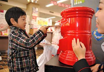 手製のグリーティングカードをポストへ投函する園児=大阪市東住吉区の東住吉郵便局