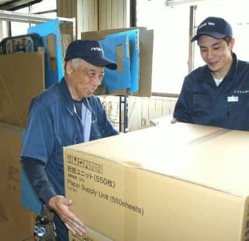 再就職先のミワテックで、運搬などの仕事に従事している野川知平さん(左)=豊後高田市
