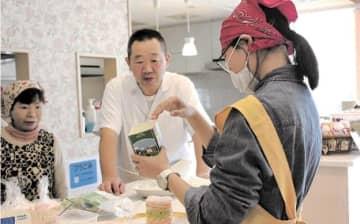 ボランティアにすしサンドの作り方をアドバイスする山口さん(中央)