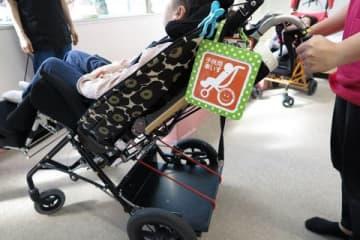 障害児らが利用するバギー型車いすは折り畳めない。オレンジ色のマークは札幌の母親グループが作製した