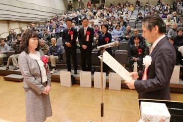 加藤副市長から表彰状を受け取る功労者(左)