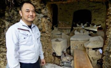 平安座の古墓「トゥダチ」を調査した沖縄国際大の宮城弘樹准教授と、墓の内部=うるま市・平安座島