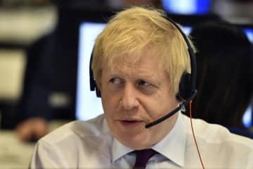 英保守党の選挙事務所で、電話で話すジョンソン英首相=8日、ロンドン(AP=共同)