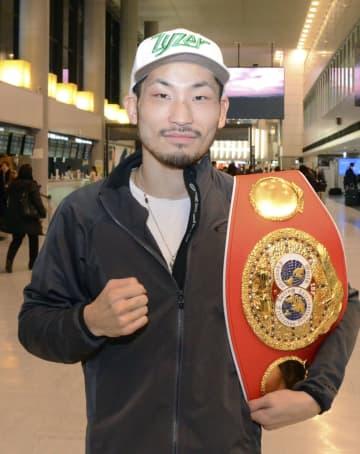 帰国し、ベルトを肩にポーズを取るIBFスーパーバンタム級王者の岩佐亮佑=9日午後、成田空港