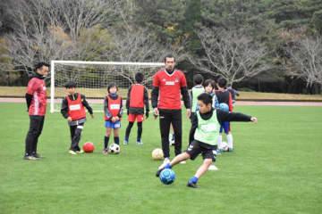 元日本代表の本田泰人さん(左)や久保竜彦さん(中央)らが児童を指導したサッカー教室