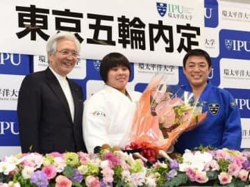 花束を贈られ、笑顔の素根輝(中央)。右は古賀稔彦総監督、左は大橋博理事長=環太平洋大