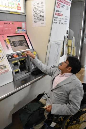 券売機の使いやすさを調べる車いす利用者=9日午後、宮崎市・JR宮崎空港駅