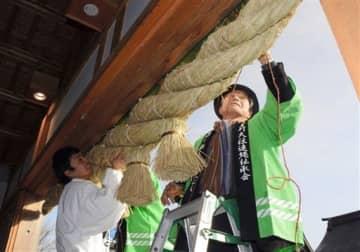 新しいしめ縄を飾り付ける伝承会員や神職=9日、阿蘇市