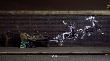 バンクシーが描いた壁画の横のベンチに寝転ぶ男性=9日、英中部バーミンガム(@banksyのインスタグラムより、ロイター=共同)