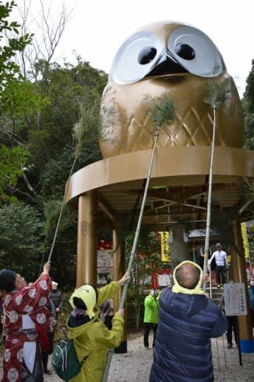 巨大フクロウ像のすす払いを行う参拝者ら=9日午前、那珂川町矢又