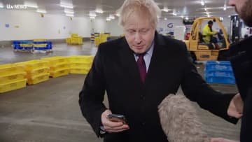 9日、英東部で、当初は見るのを拒んだ病院の男児の写真が表示された携帯電話を見るジョンソン首相(英PA通信=共同)