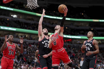Chicago Bulls guard Zach LaVine (8) goes up for a basket past Toronto Raptors center Marc Gasol (33) during the first half at the United Center Monday Dec. 9, 2019 in Chicago. - Armando L. Sanchez/Chicago Tribune/TNS