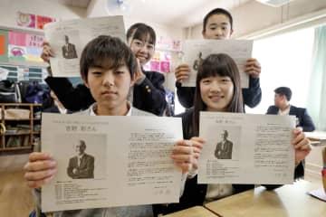 吉野彰さんからのメッセージを手にする大阪府吹田市立第一中の生徒たち=10日午後
