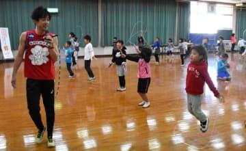 生山ヒジキさん(左)から縄跳びの上達法を教わる児童ら