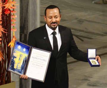 10日、ノルウェー・オスロで開かれたノーベル平和賞の授賞式で、賞状と記念メダルを受け取るエチオピアのアビー首相(共同)