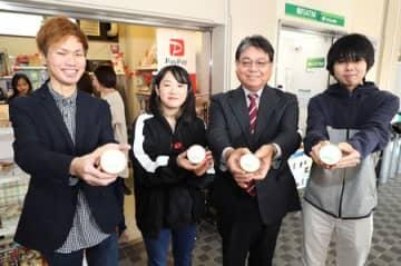 敬和学園大と粟島浦村が共同開発したアマドコロのアイスを手に笑顔の学生と本保村長(右から2人目)=新発田市