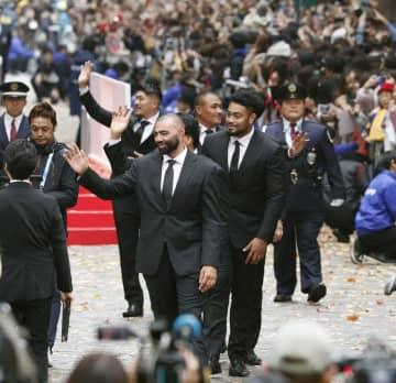 ラグビーW杯日本代表のパレードで、沿道に集まった大勢のファンに手を振るリーチ・マイケル選手(手前)、松田力也選手(奥左)ら=11日午後、東京都千代田区