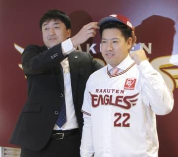 楽天の入団記者会見で石井GM(左)に帽子をかぶせてもらう牧田和久投手=11日、楽天生命パーク宮城