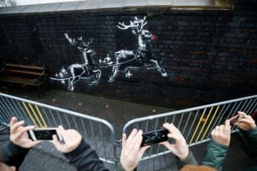 覆面ストリートアーティスト、バンクシーの新作は、2頭のトナカイが男の人をそりに乗せ、今にも飛び立とうとしている壁画で、クリスマスシーズンにぴったり。10日撮影。 - (2019年 ロイター/Henry Nicholls)