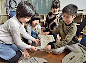 新聞をつなぎ合わせる新聞パズルに取り組む児童=11日、鳥取市気高町山宮の逢坂小