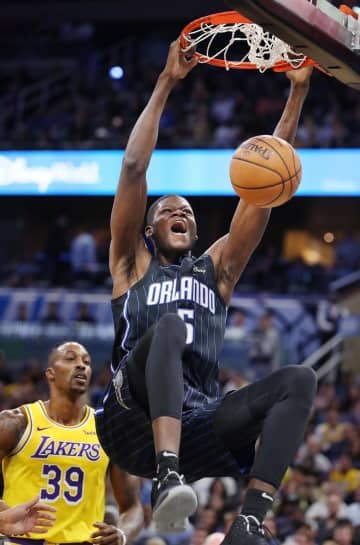 Orlando center Mo Bamba (5) screams as he slam dunks over LA center Dwight Howard (39) during the Los Angeles Lakers at Orlando Magic NBA game at the Amway Center on Wednesday, December 11, 2019. - Stephen M. Dowell/Orlando Sentinel/TNS