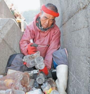 消波ブロックの間に入り、集めたペットボトルに穴を開けてまとめる尾畠春夫さん=12日午前、別府市浜脇