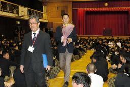 母校の宝塚中学校で講演後、花束を贈られて会場を後にするロッテ2軍監督の今岡真訪氏(中央)=宝塚市美座1