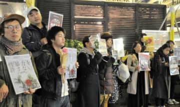 「フラワーデモ」でプラカードや生花を手にする参加者=横浜駅西口
