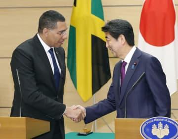 共同記者発表を終え、握手するジャマイカのホルネス首相(左)と安倍首相=12日午後、首相官邸