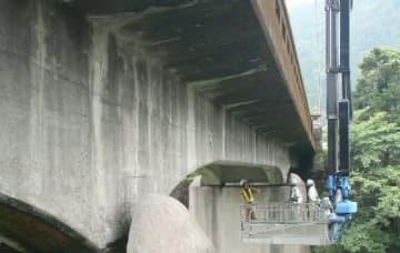 橋の点検車を使い、目視で橋の状態を確認する技術者=由布市の篠原橋
