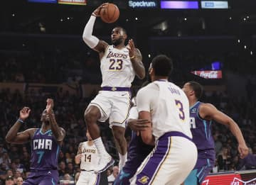 Los Angeles Lakers forward LeBron James (23) drives past Charlotte defenders during second quarter action at Staples Center. - Robert Gauthier/Los Angeles Times/TNS
