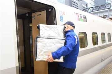 秋田新幹線こまちに運び込まれる県産野菜入りの箱=12日、JR秋田駅