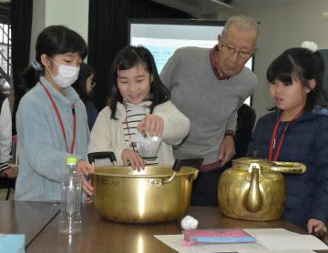 かしま子ども大学の気象の講義で古川武彦さん(右から2人目)から気圧に関する実験の指導を受ける受講生たち=鹿嶋市宮中