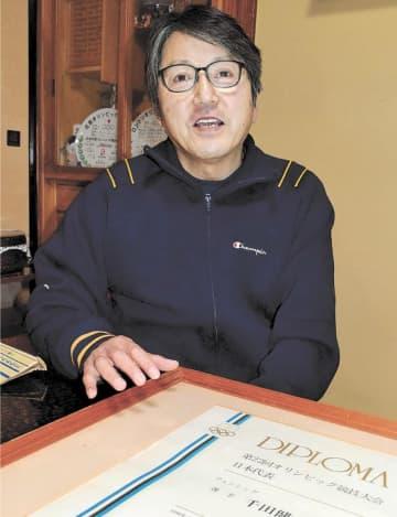 モスクワ五輪日本代表選手の認定証を前に、五輪への思いを語る千田さん=12日午後5時50分ごろ、気仙沼市松崎浦田の自宅