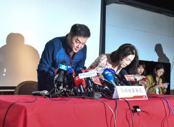 記者会見で謝罪する遠東航空の張綱維会長(左)=13日、台北(中央通信社=共同)