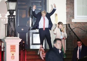 13日、両手を上げながら保守党本部を出るジョンソン英首相=ロンドン(ロイター=共同)