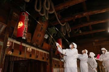 篠竹を使って、ほこりを落とす神職ら=三之宮比々多神社