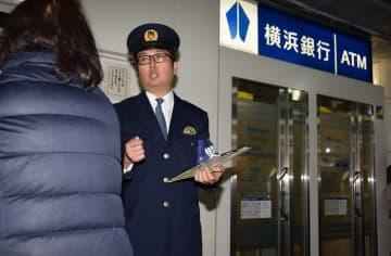 ATM利用者に特殊詐欺への注意を呼びかける警察官=横浜市西区
