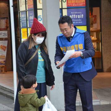 チラシを配り市民に情報提供を求める捜査員=JR平塚駅北口