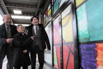 ラッピングされた駅舎を眺める八重樫さん(中央)