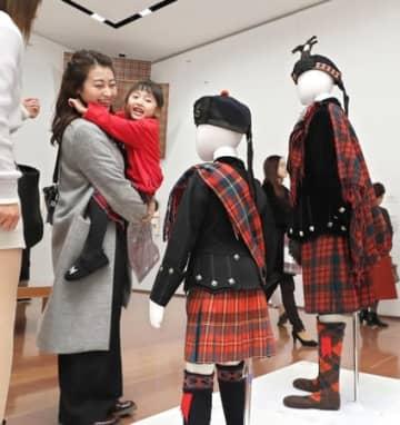 「タータン展」の展示を見て笑顔を浮かべる来場者=13日、新潟市中央区