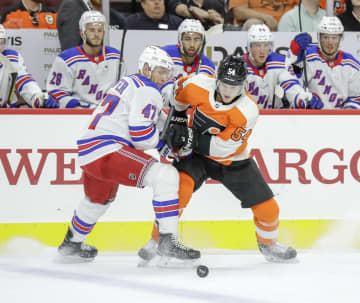 The Philadelphia Flyers' Oskar Lindblom, right, goes after the puck against the New York Rangers' Steven Kampfer during a preseason game on September 26, 2017, at the Wells Fargo Center in Philadelphia. - YONG KIM/Philadelphia Daily News/TNS