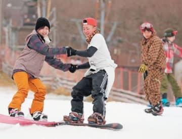 オープンした九重森林公園スキー場で、初滑りを楽しむスノーボーダーら=14日午前、九重町