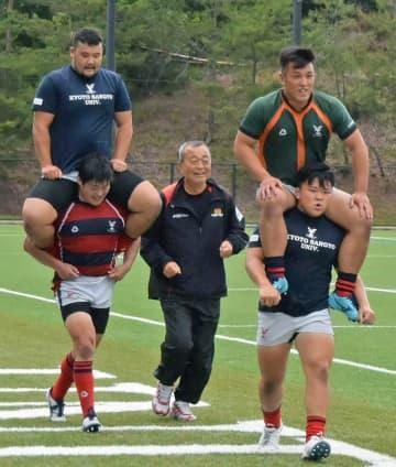 FW選手と一緒にグラウンドを走る京都産業大の大西監督(中央)=京都市北区・神山球技場